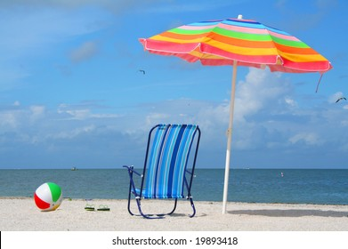 Beach chair, ball and umbrella on a summer day.