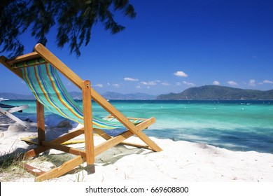 Beach chair on the beach, The beach has white sand, trees, blue sky and clouds. The beach is located in a phuket island, Phuket has many beaches and is popular with tourists around the world.