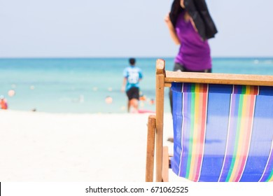 Beach chair On the white beach The background is a blurred image of tourists going to sea.