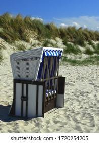 Strandstuhl auf weißem Sand der Ostsee vor einer Düne.
