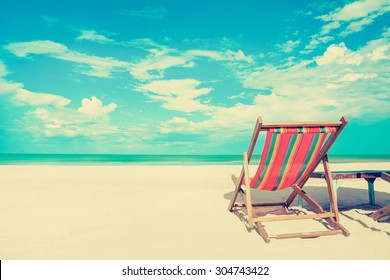 Beach chair on white sand beach in sunny sky background, vintage tone - summer holiday concept