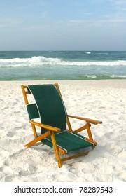 Beach chair on white sand beach.