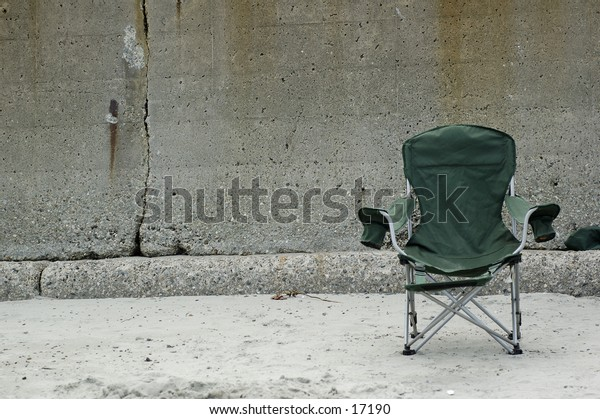 Beach chair in the sand against concrete wall