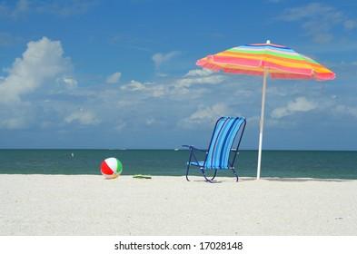 Beach chair, umbrella, flip-flops and ball on a sunny day at the beach