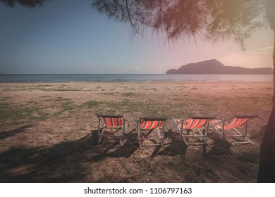 Beach chair under the tree at empty sand beach with blue sea
