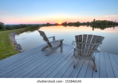 Beach chairs along pond at sunset