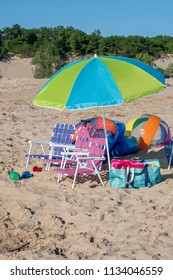 beach chairs and colorful beach toys are grouped in a vacation still life on a sunny beach