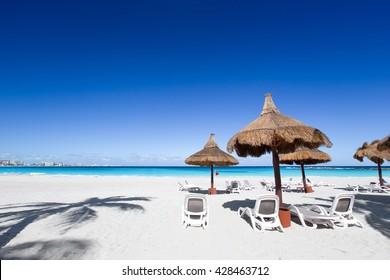 Beach chairs and grass umbrellas on a stunning tourist resort beach