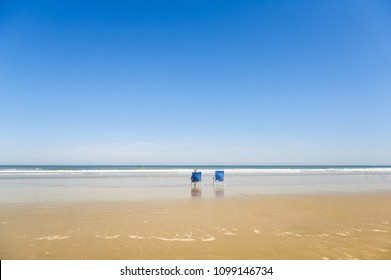 Beach chairs lined up in front of the blue waters of the sandy Cocoa Beach, Florida, USA.