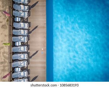 Beach chairs near swimming pool, top view