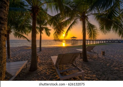 Beach chairs on beach with beautiful beach and tropical sea at sunset.