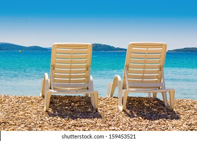 Beach chairs on pebble beach, beautiful blue sky and sea, island in background