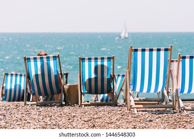 Beach chairs on the beach with a sailboat in the background