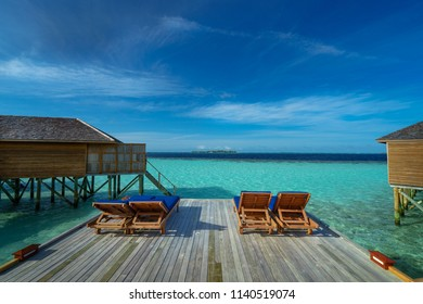 Beach chairs on wooden terrace over blue sea and sky, Maldives
