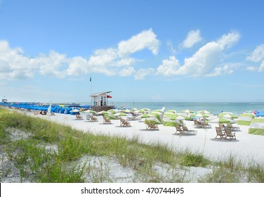 Beach chairs and parasols on beautiful white sand beach . Sand dunes, blue sky with clouds, and green ocean in the background.  Gulf of Mexico, Clearwater Beach, Florida, USA.