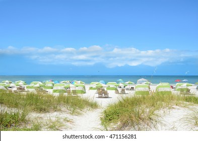 Beach chairs and parasols on beautiful white sand. Sand dunes, blue sky with clouds, and green ocean in the background.  Gulf of Mexico, Clearwater Beach, Florida, USA.