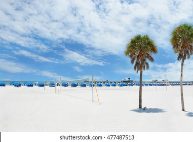 Beach chairs and parasols on beautiful white sand.  Palm trees, fishing pier, blue sky with clouds, and green ocean in the background.  Gulf of Mexico, Clearwater Beach, Florida, USA.