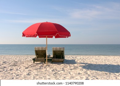 Beach Chairs with Red Umbrella on White Sandy Beach