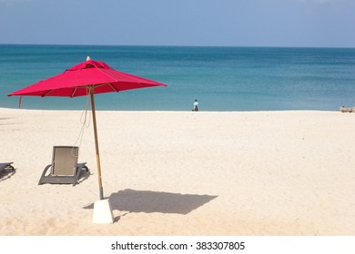 Beach chairs and red umbrella on the beach