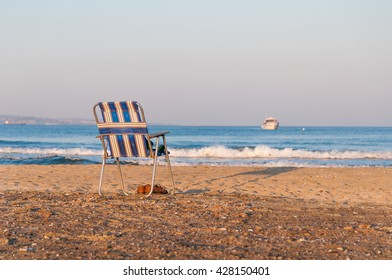 Beach chairs/ A beach scene with chair , shoes , clothes on the chair and boat.
