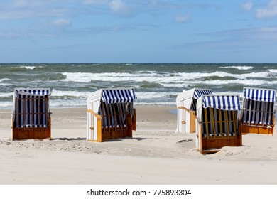 Beach chairs with sunscreens in Kolobrzeg in Poland can be seen on a sandy beach by the shore line on the Baltic Sea