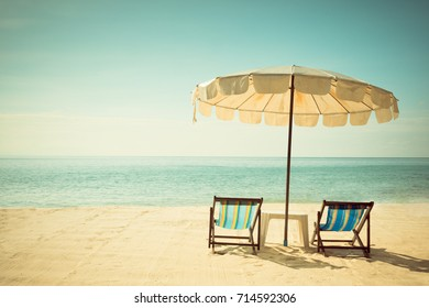 beach chairs and umberella on tropical ocean beach