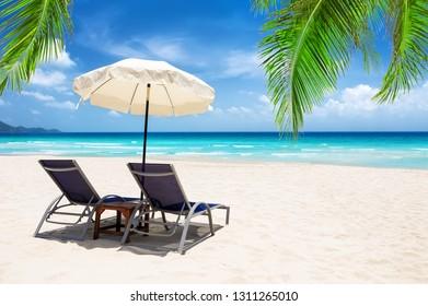 Beach chairs with umbrella and beautiful sand beach in Koh Samui, Thailand