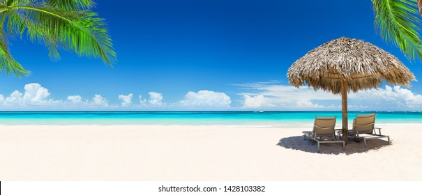 Beach chairs with umbrella and beautiful sand beach in Punta Cana, Dominican Republic. Panorama of tropical beach with white sand and turquoise water. Travel summer holiday background concept.