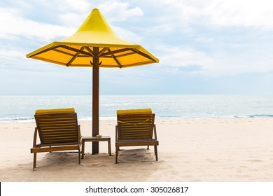 Beach chairs with umbrella and beautiful sand beach