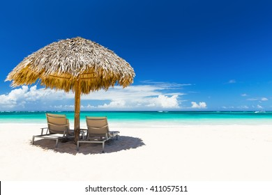 Beach chairs with umbrella and beautiful sand beach in Punta Cana,