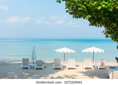 Beach chairs with umbrella with blue sky on tropical beach