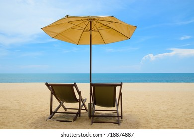 Beach chairs and umbrella on beautiful sand beach with cloudy and blue sky