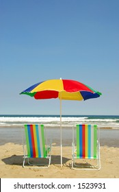 Beach chairs and umbrella on the ocean shore with surf in the background