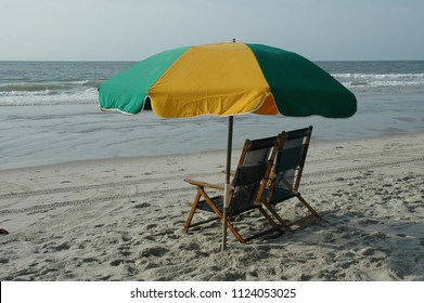 Beach chairs and umbrella at the seashore.