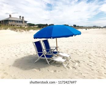 Beach chairs and umbrella at the seashore.