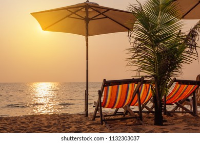 Beach chairs with umbrella at sunset time on the tropical island