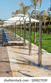 beach chairs and umbrellas along a pool