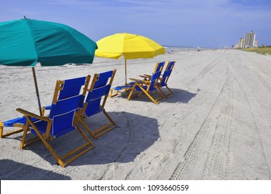 Beach chairs and umbrellas offer welcoming shade on a hot Summer day at the seashore.