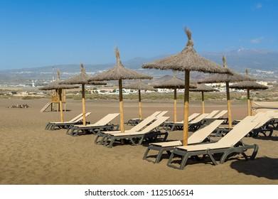 Beach chairs and umbrellas of Playa de Tejita sand. Tenerife, Spain.