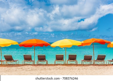 Beach chairs and umbrellas vacation background - colorful parasols lined up on sand of Sint Maarten beach, Dutch Antilles, Caribbean island. Tropical travel holiday landscape.