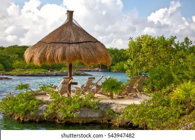 Beach chairs under a thatch hut on a tropical beach