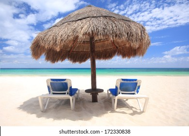 Beach chairs under thatched umbrella overlooking a tropical beach, Cozumel Mexico.