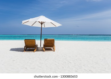 Beach chairs with a view of clear blue water in the Maldives
