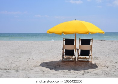 Beach chairs with yellow sun umbrella by the ocean.
