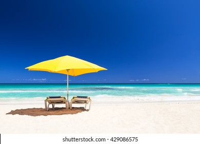 Beach chairs with yellow umbrella and beautiful sand beach in Punta Cana, Dominican Republic
