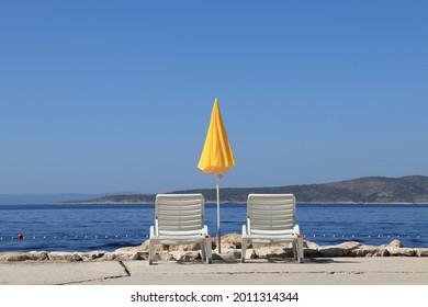 Beach chairs and yellow umbrella near Adriatic sea