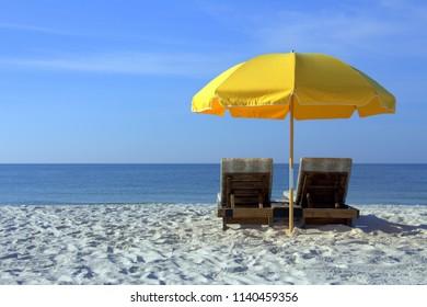 Beach Chairs with Yellow Umbrella on White Sandy Beach