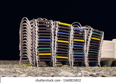 Beach chaise lounges stacked in a row on the night rocky beach
