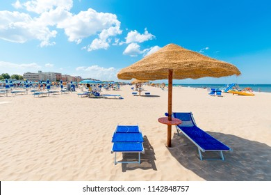 Beach with clean white sand. Rimini beach on a sunny day. Sun umbrella and deck chairs on seaside on blue sky background.