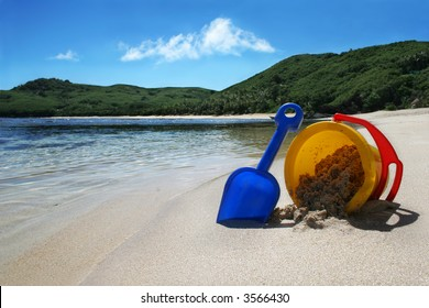 beach with clear blue water on tropical island with childrens toy bucket and spade, concept holiday
